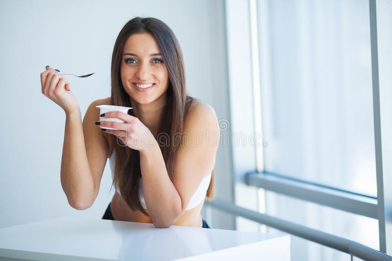 Glimlachend meisje met yoghurt Jonge glimlachende Vrouw die Verse Organische Yoghurtzitting in witte heldere ruimte proeven, die  royalty-vrije stock afbeelding