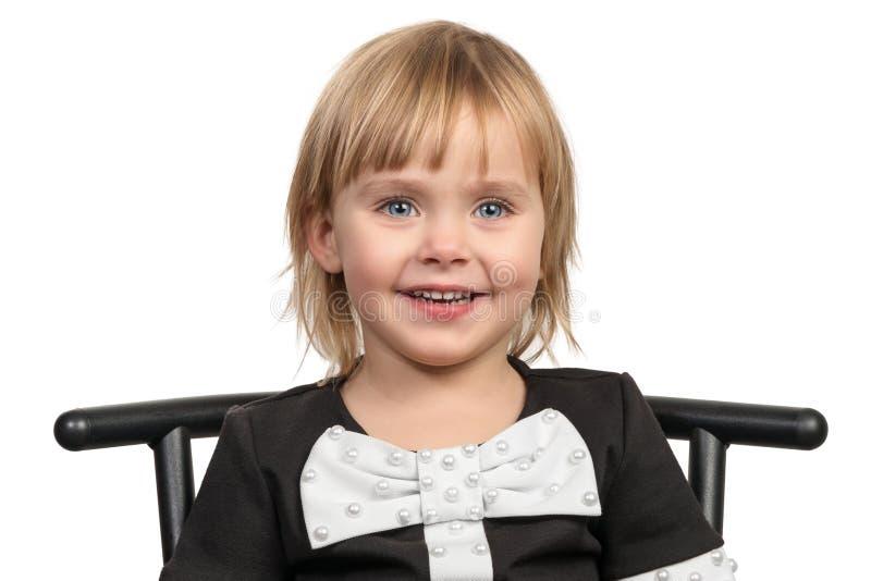 Glimlachend meisje op een stoel stock afbeelding