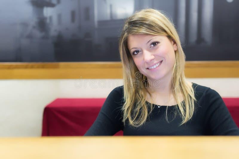 Glimlachend meisje op het ontvangstbureau stock fotografie