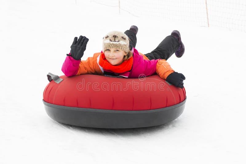 Glimlachend Meisje Snowtubes bergaf stock foto's