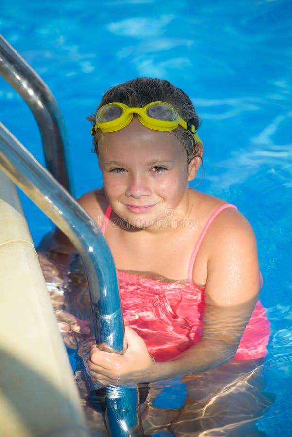 Glimlachend meisje in zwemmende beschermende brillen in het zwembad stock fotografie