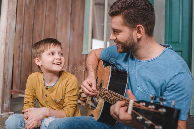 Glimlachend mens het spelen gitaar met dichtbij langs zoon stock afbeelding