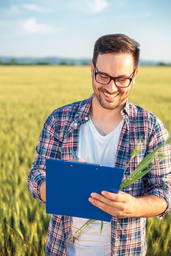 Glimlachend millennial agronoom of landbouwers het inspecteren tarwegebied vóór de oogst, het schrijven gegevens aan een klembord stock foto