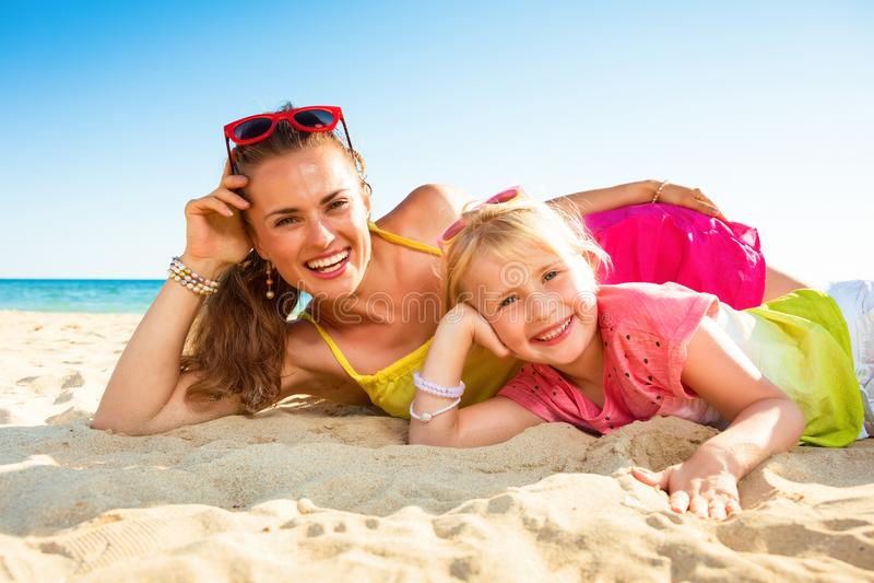 Glimlachend modern moeder en kind bij kust het leggen stock afbeeldingen