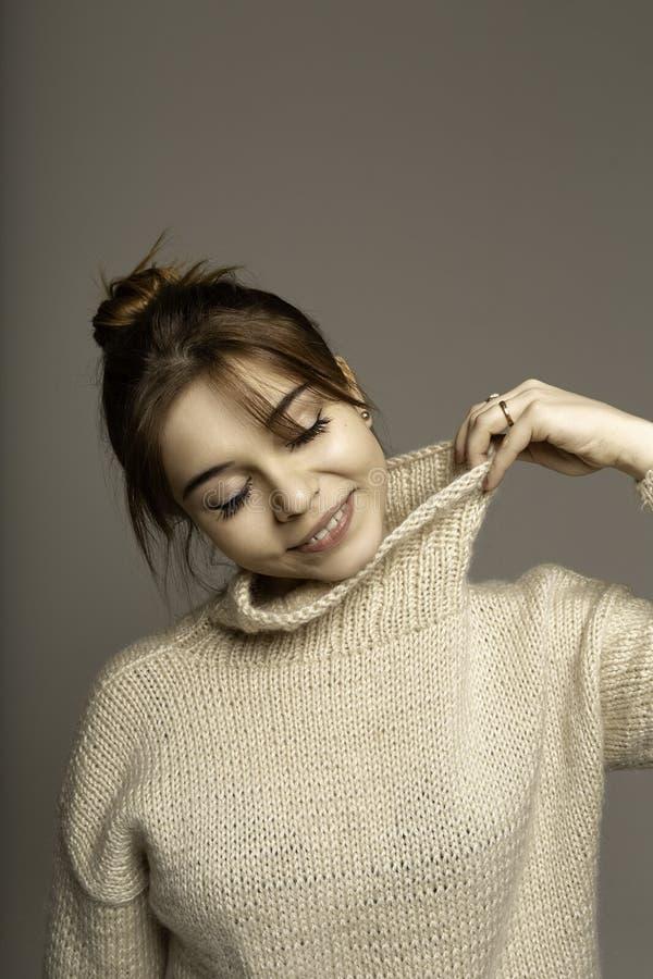 Glimlachend mooi donkerbruin meisje in beige sweater royalty-vrije stock fotografie