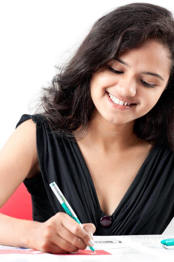 Glimlachend mooi Indisch meisje dat op papier schrijft royalty-vrije stock afbeeldingen