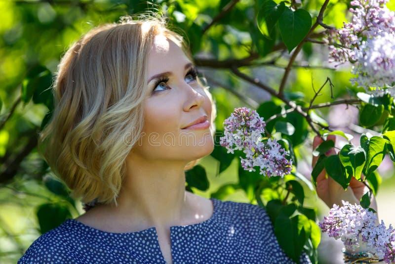 Glimlachend mooi jong blond meisje dichtbij lilac struik royalty-vrije stock afbeelding