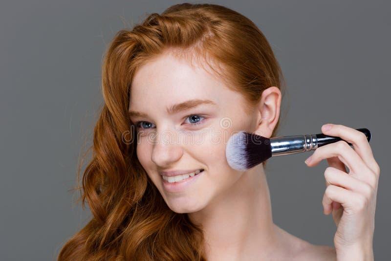 Glimlachend mooi jong vrouwelijk het van toepassing zijn poeder bloos borstel voor make-up stock foto