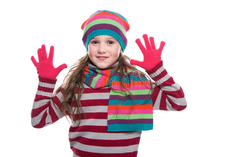 Glimlachend mooi meisje die kleurrijke gebreide die sjaal, hoed en handschoenen dragen op witte achtergrond wordt geïsoleerd De w stock fotografie
