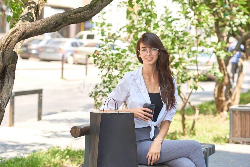 Glimlachend mooi meisje die koffie houden, die op houten bank dichtbij document zakken zitten royalty-vrije stock afbeelding