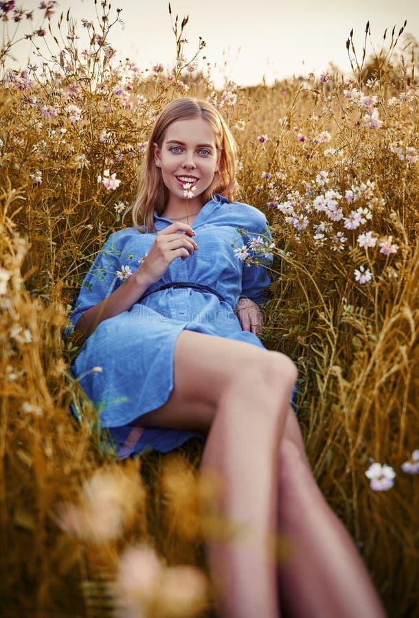 Glimlachend mooi meisje die onder gras en bloemen liggen Openluchtportret van aantrekkelijke jonge vrouw in blauwe kleding stock fotografie