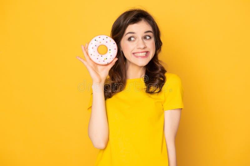 Glimlachend mooi meisje die zoete doughnut in hand houden royalty-vrije stock afbeelding