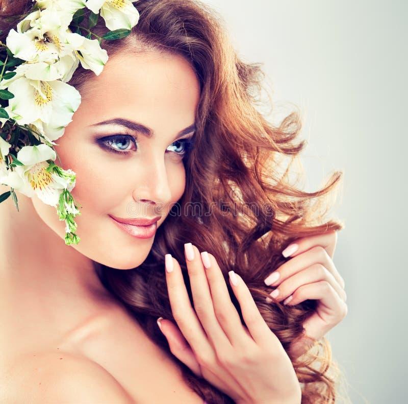 Glimlachend mooi meisje Gevoelige pastelkleurbloemen in krullend haar royalty-vrije stock afbeelding