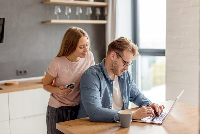 Glimlachend mooi meisje het controlerende werk van haar echtgenoot aangaande laptop royalty-vrije stock fotografie