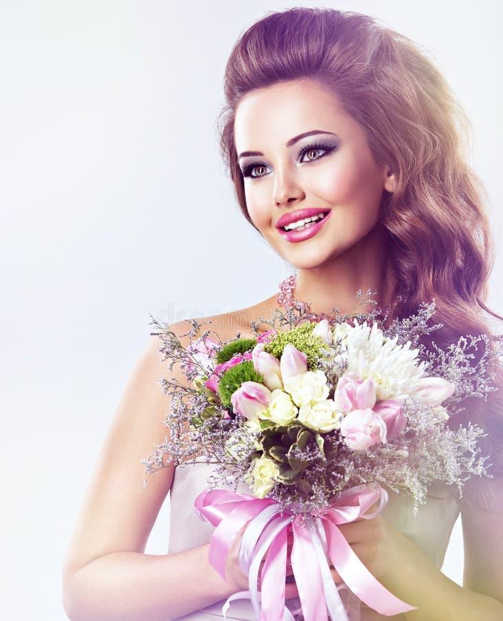 Glimlachend mooi meisje met bloemen in handen stock afbeeldingen
