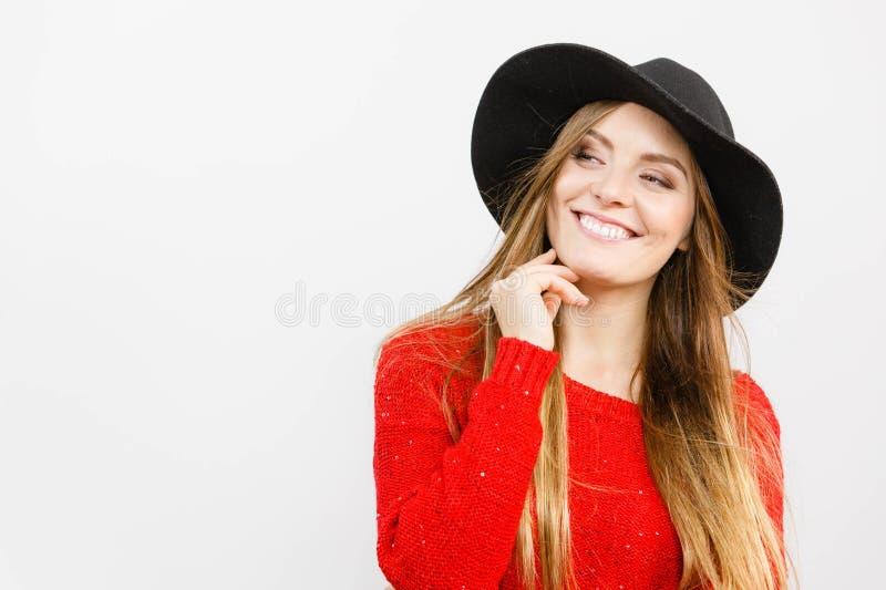 Glimlachend mooi meisje met bruin haar en zwarte hoed stock foto