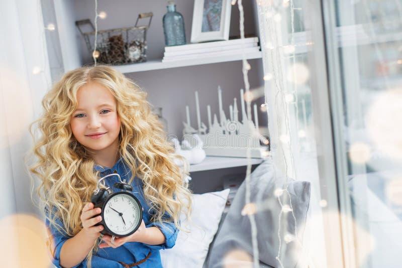 Glimlachend mooi meisje met een klok bij handen dichtbij het venster royalty-vrije stock fotografie