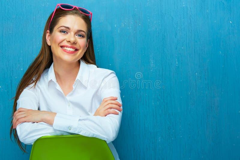Glimlachend mooi meisje op groene stoelzitting stock afbeelding