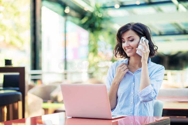 Glimlachend mooi wit Kaukasisch meisje met zwarte krullende haarzitting in straatbar en het gebruiken van haar telefoon royalty-vrije stock afbeelding