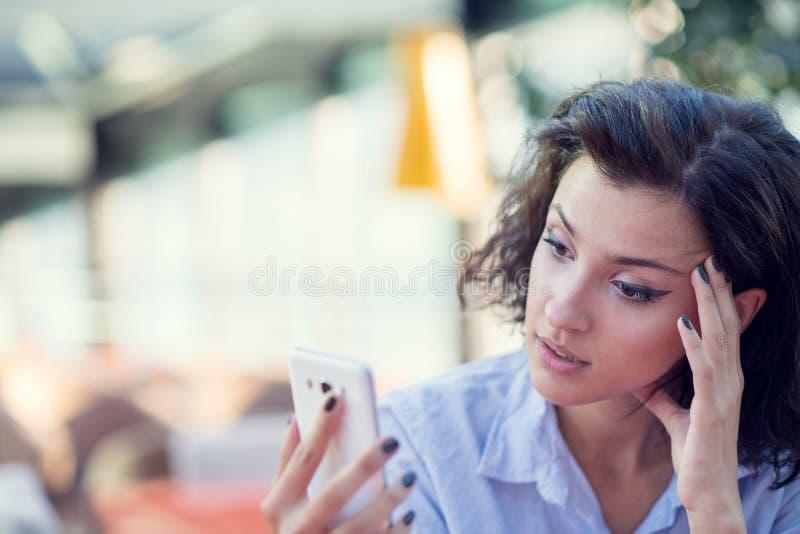 Glimlachend mooi wit Kaukasisch meisje met zwarte krullende haarzitting in straatbar en het gebruiken van haar telefoon stock fotografie