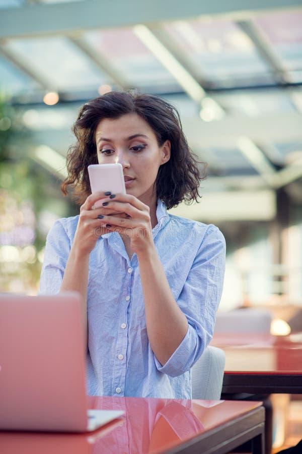 Glimlachend mooi wit Kaukasisch meisje met zwarte krullende haarzitting in straatbar en het gebruiken van haar telefoon stock afbeeldingen