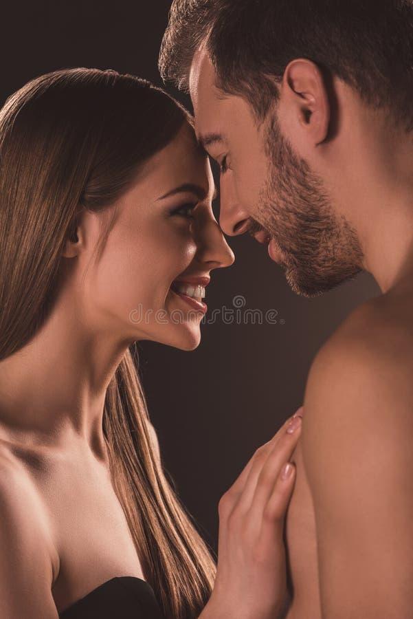 glimlachend naakt paar die en elkaar koesteren bekijken, royalty-vrije stock foto