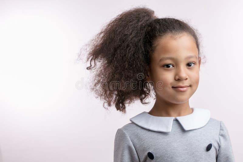 Glimlachend ontzagwekkend schoolmeisje die in modieuze in kleding de camera bekijken royalty-vrije stock afbeelding