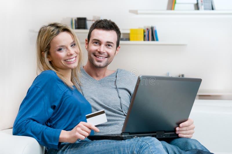 Glimlachend paar dat online het winkelen maakt stock foto