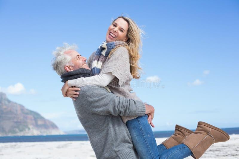 Glimlachend paar dat pret op het strand in warme kleding heeft royalty-vrije stock afbeelding