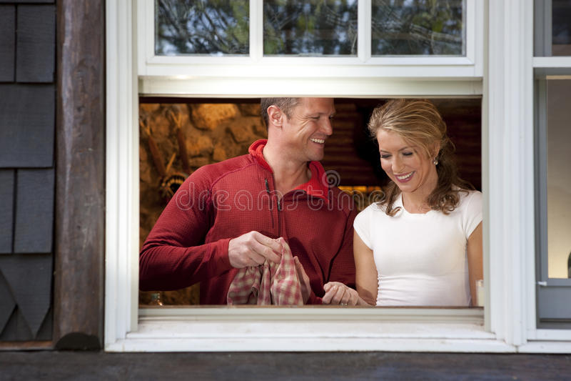 Glimlachend Paar dat Schotels doet bij het Venster van de Keuken stock afbeeldingen