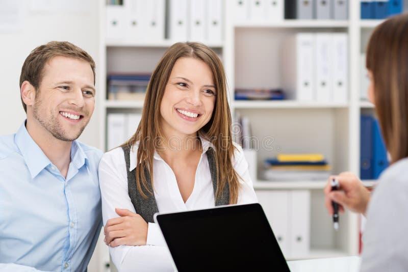 Glimlachend paar die aan een bedrijfsmakelaar babbelen stock foto's
