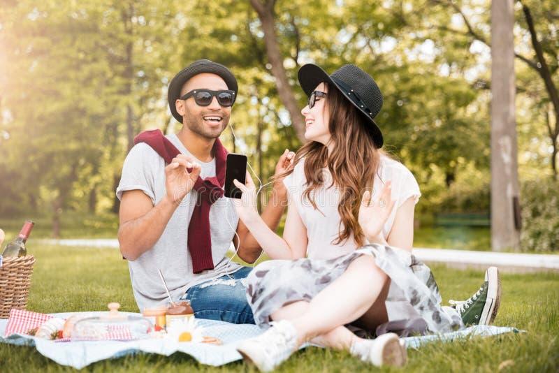 Glimlachend paar die aan muziek van celtelefoon luisteren op picknick royalty-vrije stock foto's