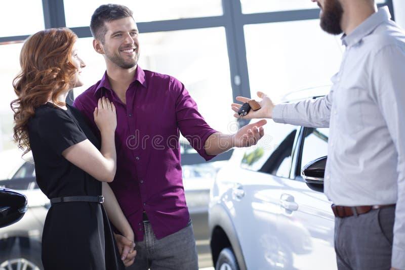 Glimlachend paar die autosleutels van een handelaar in een toonzaal krijgen stock foto's