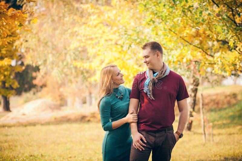Glimlachend paar die in de herfstpark koesteren stock afbeelding