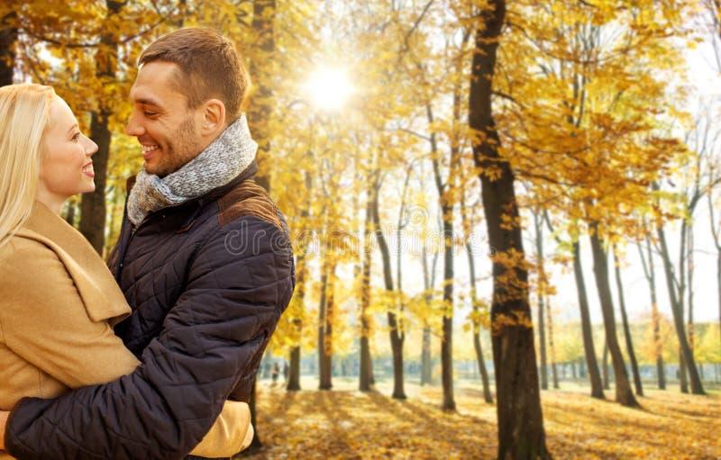 Glimlachend paar die in de herfstpark koesteren stock afbeeldingen