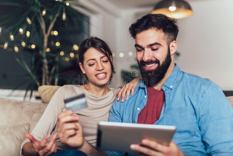 Glimlachend paar die digitale tablet en creditcard gebruiken royalty-vrije stock foto