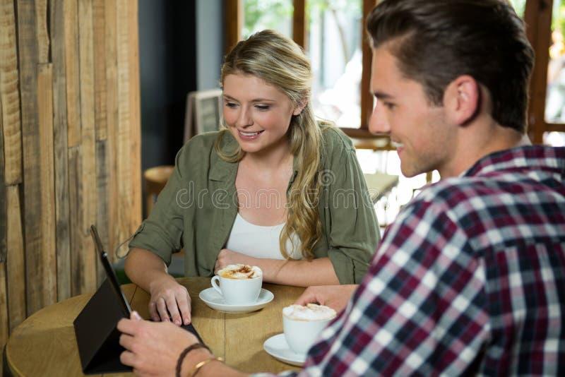 Glimlachend paar die digitale tablet gebruiken bij lijst in koffie stock fotografie