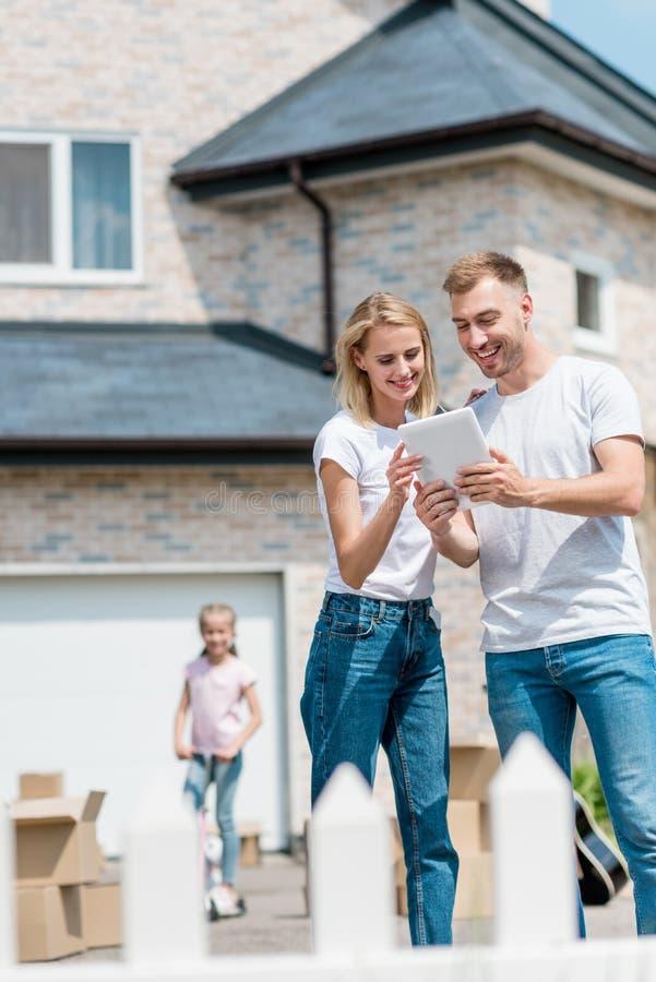 glimlachend paar die digitale tablet gebruiken terwijl hun dochter die op schopautoped erachter berijden in yard van nieuw royalty-vrije stock fotografie