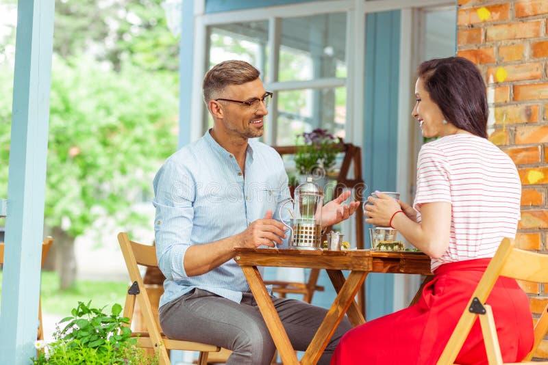 Glimlachend paar die een gesprek hebben terwijl het zitten in een koffie royalty-vrije stock foto