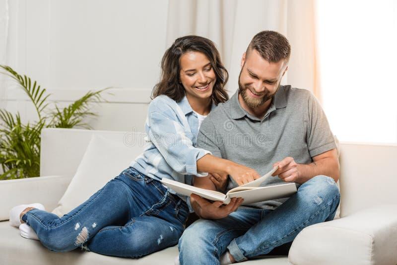 Glimlachend paar die fotoalbum bekijken en op bank thuis zitten stock foto's