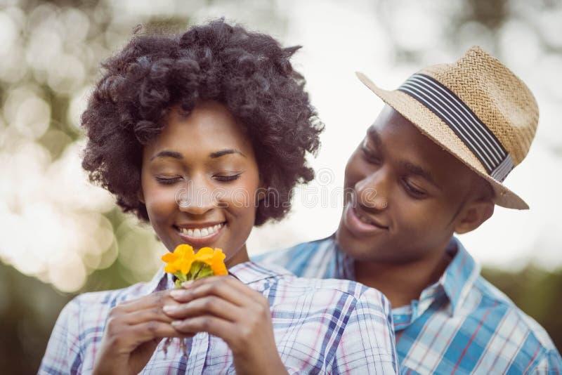 Glimlachend paar die gele bloemen houden royalty-vrije stock fotografie