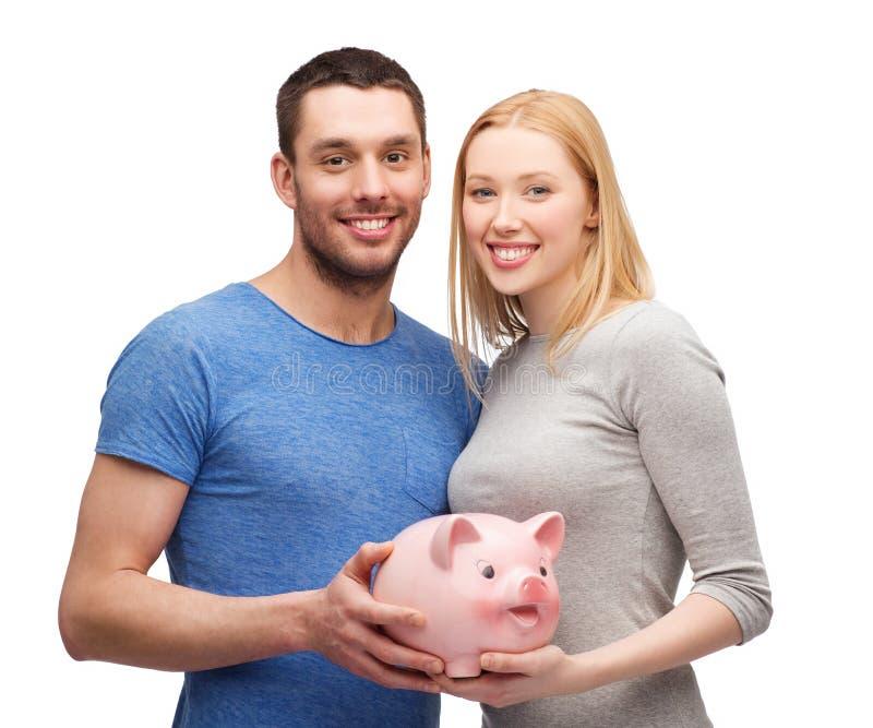 Glimlachend paar die groot spaarvarken houden royalty-vrije stock afbeeldingen