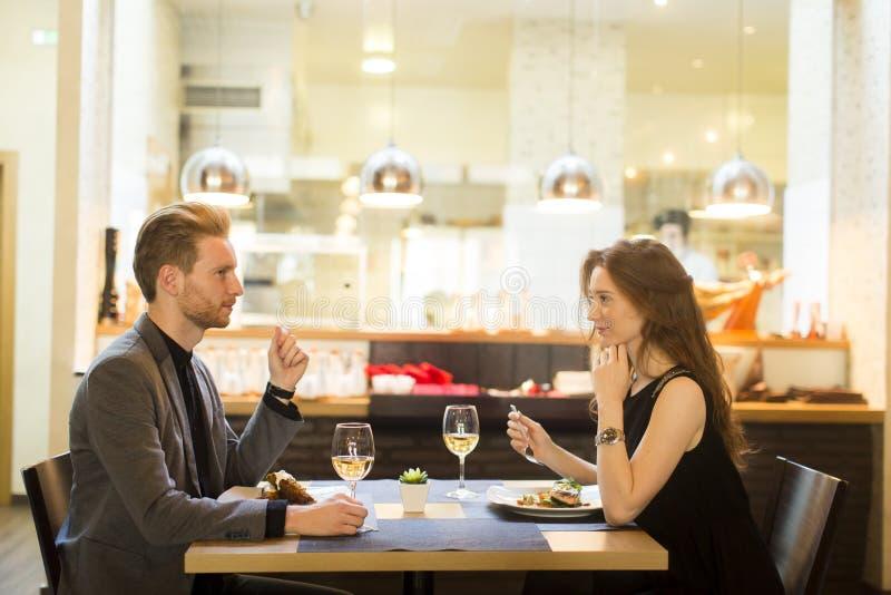 Glimlachend paar die hoofdgerecht eten bij restaurant royalty-vrije stock fotografie
