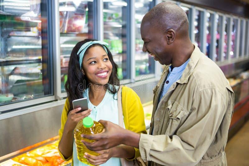 Glimlachend paar die in kruidenierswinkelsectie winkelen stock foto's