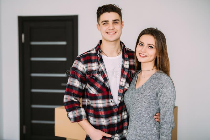 Glimlachend paar die op dozen in nieuw huis leunen Jong paar die aan een nieuwe flat zich samen verhuizing bewegen stock fotografie