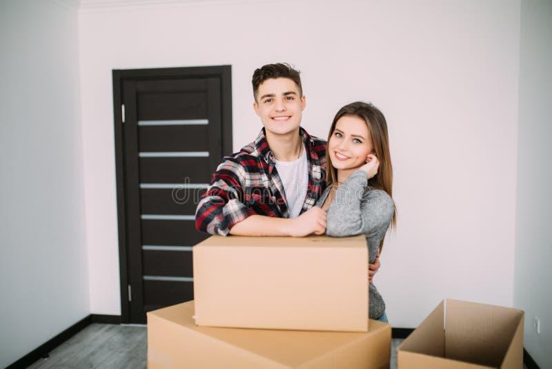 Glimlachend paar die op dozen in nieuw huis leunen Paar in nieuwe apparment na zich het bewegen royalty-vrije stock foto