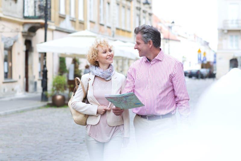 Glimlachend paar die op middelbare leeftijd met kaart elkaar bekijken terwijl het lopen in stad royalty-vrije stock fotografie