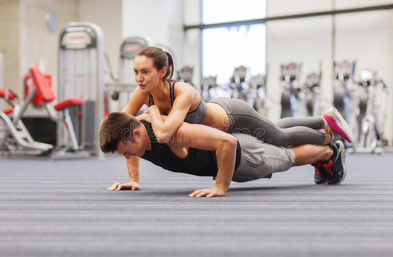 Glimlachend paar die opdrukoefeningen in de gymnastiek doen royalty-vrije stock foto's