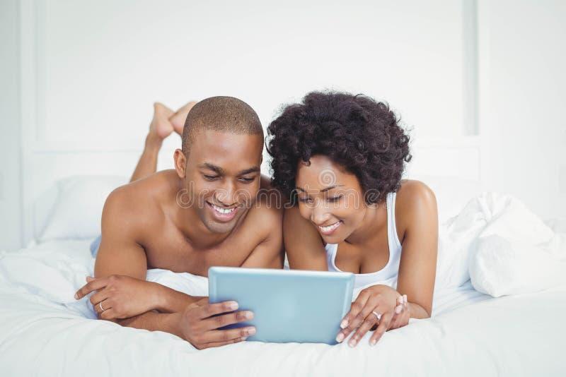 Glimlachend paar die tablet op bed gebruiken royalty-vrije stock fotografie
