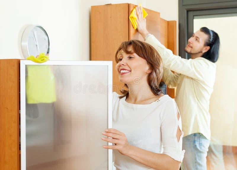 Glimlachend paar die thuis schoonmaken stock fotografie